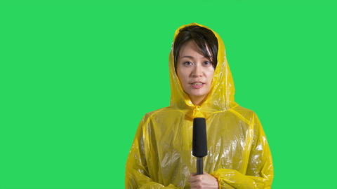 Chinese news reporter reporting storm on green screen Footage