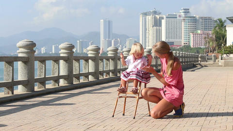 Blonde Girl in Sits on Chair and Mother Claps Footage