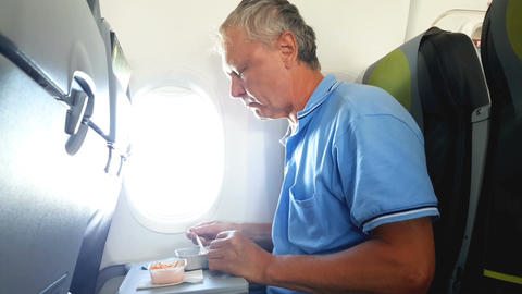Man eats on the plane Image