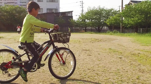 A boy riding a bicycle in a park square ビデオ