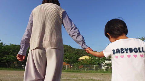 Parent and child walking hand in hand Footage
