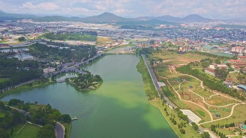 Flycam Moves over Beautiful Quiet Lake against Modern City Footage