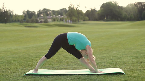 Healthy adult woman doing yoga exercises outdoors Stock Video Footage