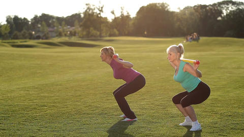 Slim adult women doing squats with bodybar in park Live Action