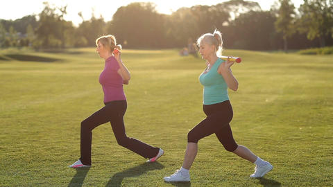 Fit adult women doing forward lunges with body bar Footage