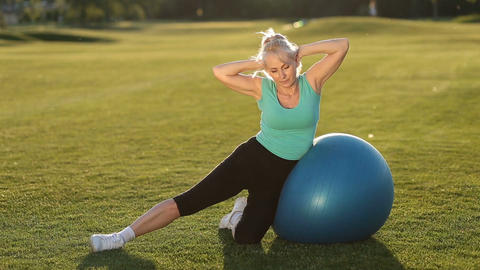 Sporty fit lady doing side crunches on ball Live Action
