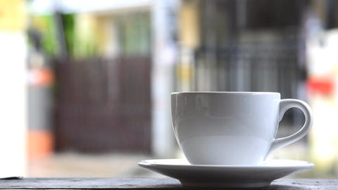 Steaming coffee cup on a rainy day Filmmaterial