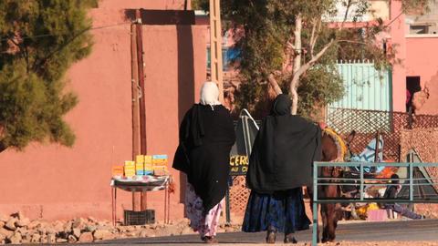 Women in paranja in Sahara village smooth zooming Footage