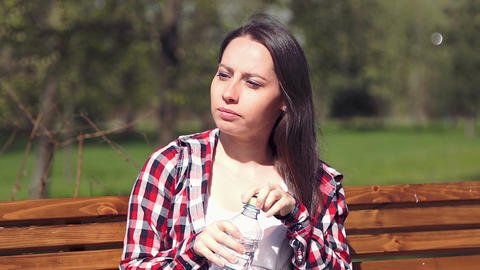 Young girl 20s drinking water from bottle in park Footage