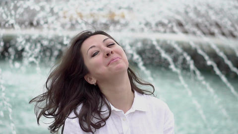 A young woman sits near a fountain and fixing hair Footage