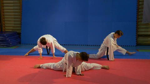 Three young men wearing karate kimonos doing stretching exercises at the gym Footage