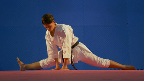 Man karate practitioner sitting in twine position on the floor and stretching hi Footage