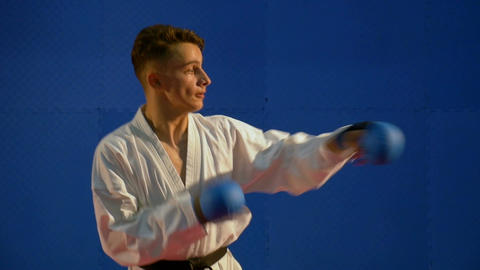 Young kick box practitioner kicking and punching wearing special equipment glove Footage