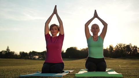 Women yoga meditating in lotus pose hands overhead Footage