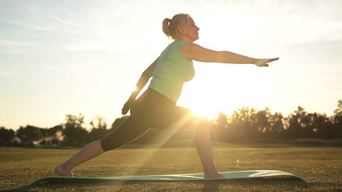 Adult healthy woman practicing yoga at sunset Live Action
