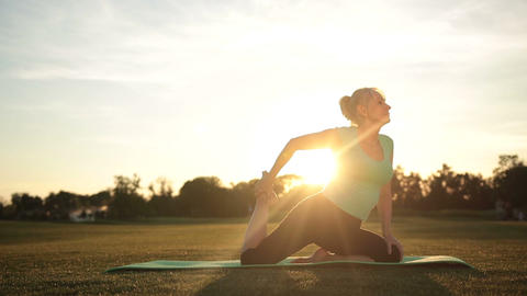 Fit woman training in yoga pigeon pose at sunset Footage