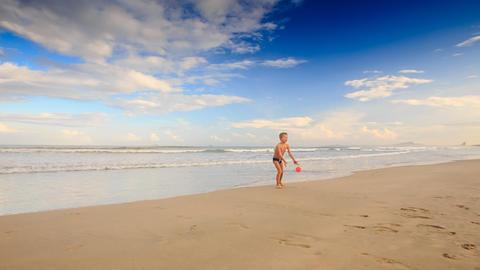 Little Blond Boy Kicks Red Ball on Wet Sand Beach Footage