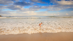 Little Blond Boy Gambols in Foamy Waves of Shallow Sea on Beach Footage