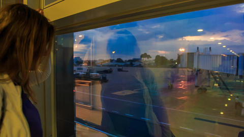 Backside Girl Watches Evening Airport Reflection in Window Footage