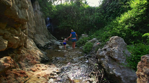 Little Girl Holds Mom Hand Jumps on Stones in Stream Footage