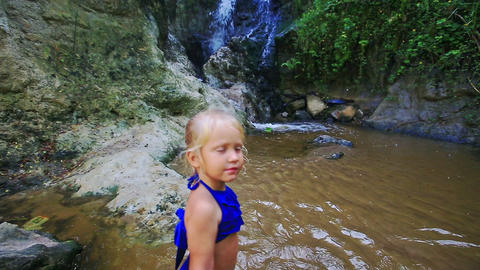 Small Girl Walks in Stream Water to Waterfall Footage