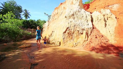 Mom Daughter Walk along Stream Turn Around Sunny Cliff Footage
