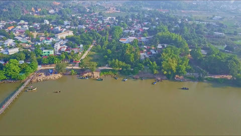 Drone Flies from Town on Bank across Wide River with Bridge Footage