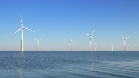 Wind turbines with turning blades in the wind in an offshore windpark Footage