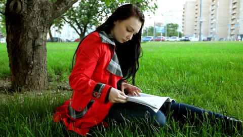 Brunette Reading a Magazine Resting on the Grass Footage