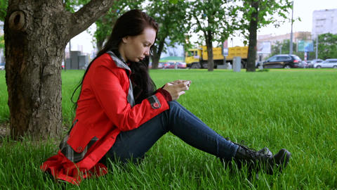 Young woman sitting on the grass and sending sms Footage
