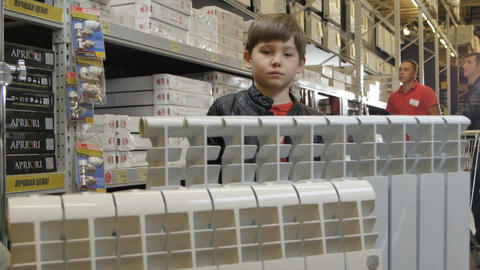 Boy Plays with Toy Cat at Heaters in Hardware Store Footage