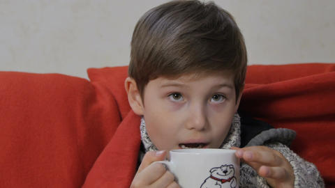 Boy in Soft Sweater Sits on Sofa under Red Blanket Live Action