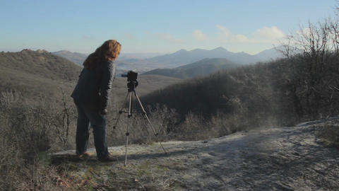 Woman make a shot of landscape with camera on the tripod at autumn Footage