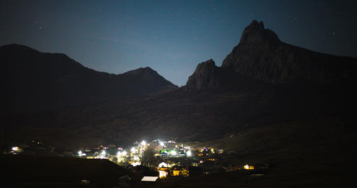 Stars over the night mountain valley with lights of the village. Timelapse video Footage