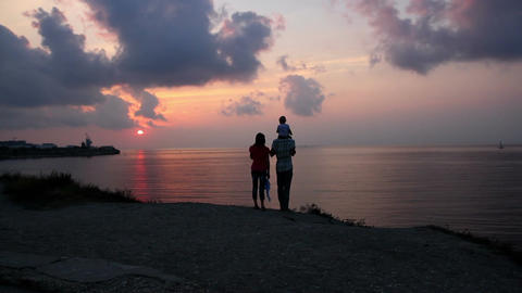 A family with a small child admiring the sea sunset on the beach Footage