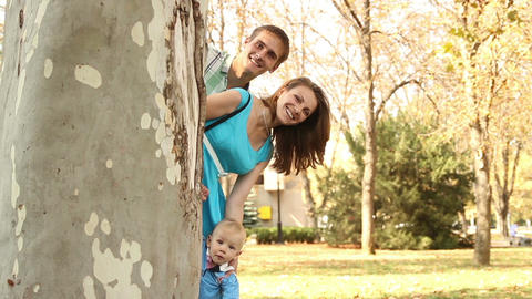 Family peeking out from behind tree trunk and smiling Footage