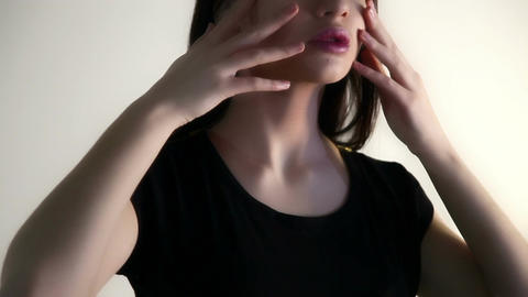 A woman holds her fingers over the face, neck, collarbone Live Action