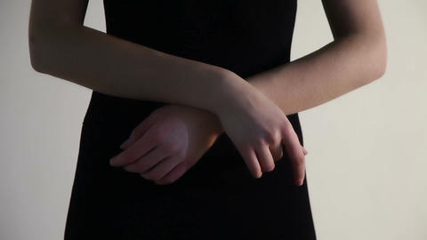 A young woman touches her wrists over the arm Live Action