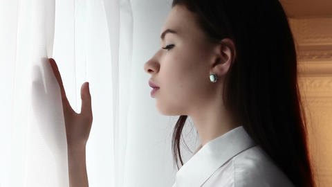 Young woman waiting near the curtains in shirt Live Action
