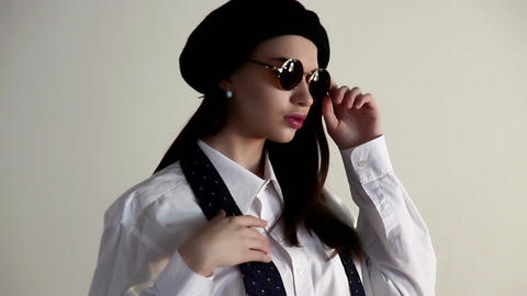 A young woman in a shirt, tie and beret, asks for a silence Stock Video Footage