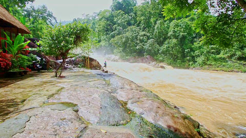 Wide Stormy Mountain River Swirls by High Smooth Rocky Bank Footage