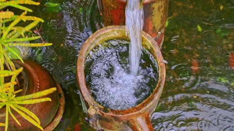Closeup Water Pours from Fountain Cascade into Pond in Park Footage
