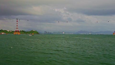 Camera on Boat Speeds across Azure Sea along Rope-way Footage