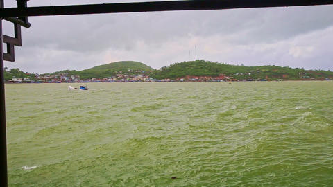 Azure Sea Single Boat Sailing in Waves against Hilly Island Footage