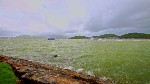 Azure Sea Waves Break at Rocky Bank against Cloudy Sky Footage