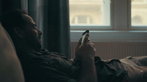 Man laying at home using his smartphone Footage