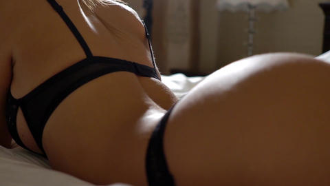 Young woman in lingerie seductively laying in bed Footage