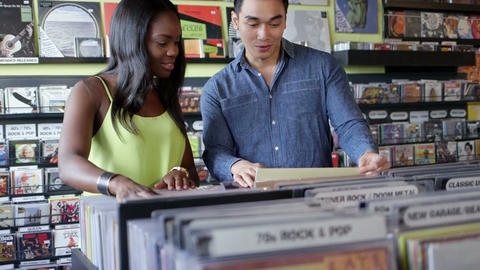Upward Panning MS A Young Woman and Young Man flick through vintage records toge Footage
