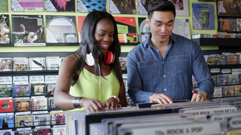 MS A Young Woman and Young Man flick through vintage records together Live Action