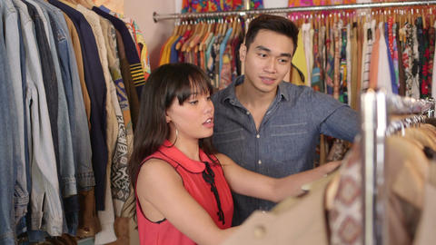 MS A Young Woman and a young Man browse through a shop of colourful vintage clot Live Action